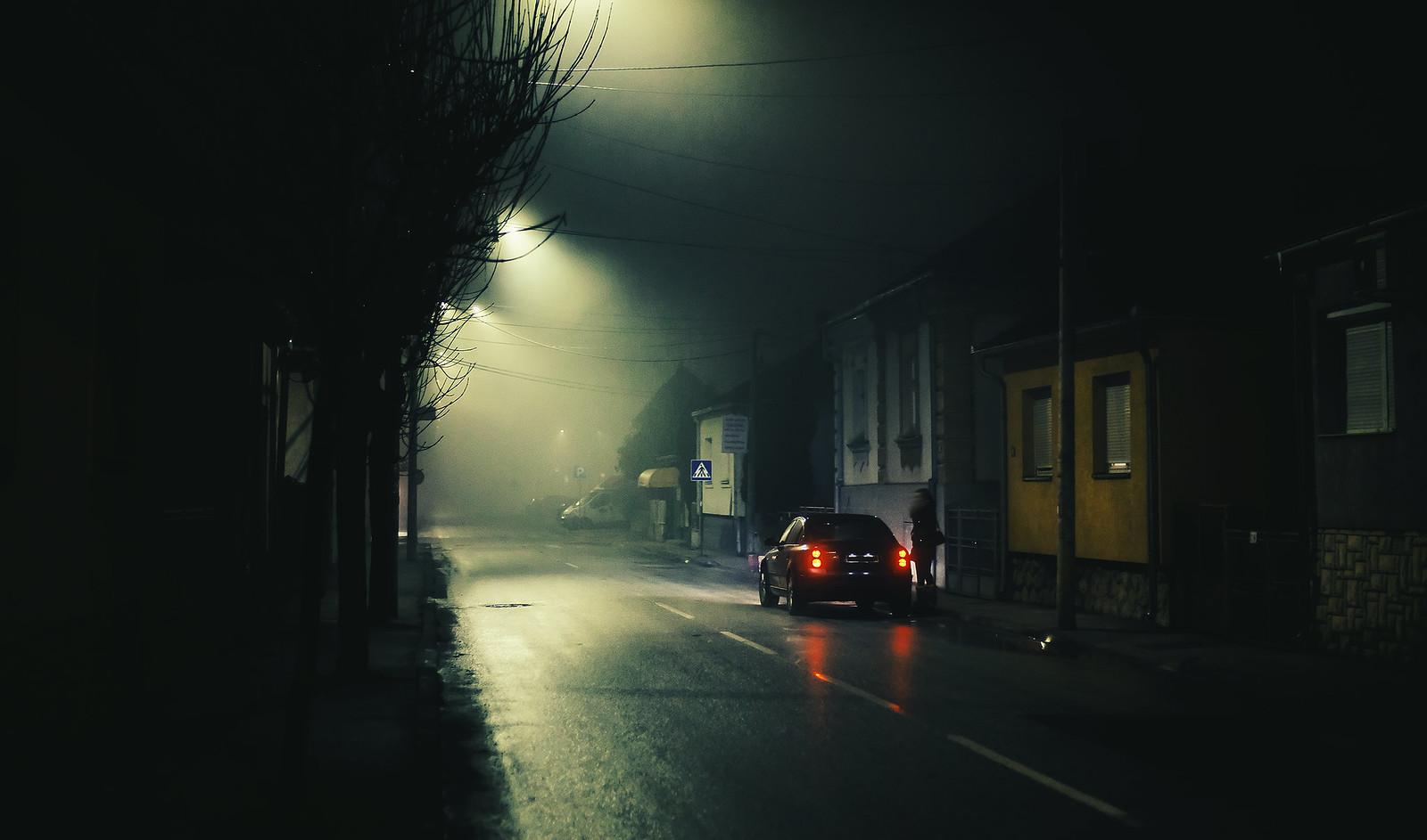 Mujer por una calle solitaria y oscura
